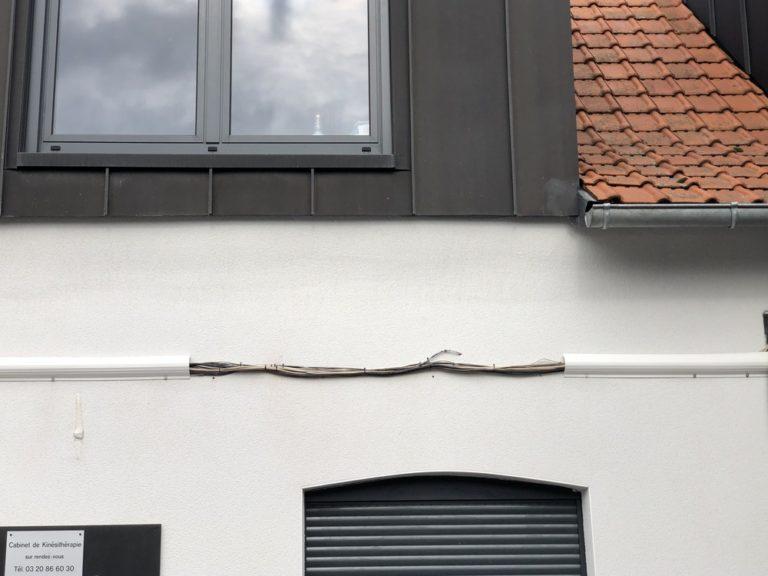 Façade en cours de pose de Cable Cover, le cache cables des facades de batiments